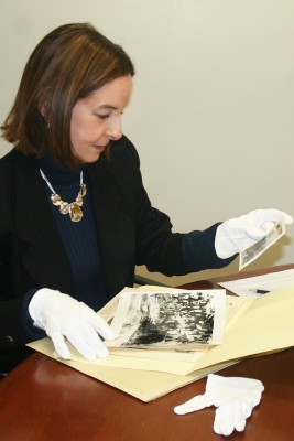 Dr. Cheryl Beck examining vintage photographs from the Dolan Collection